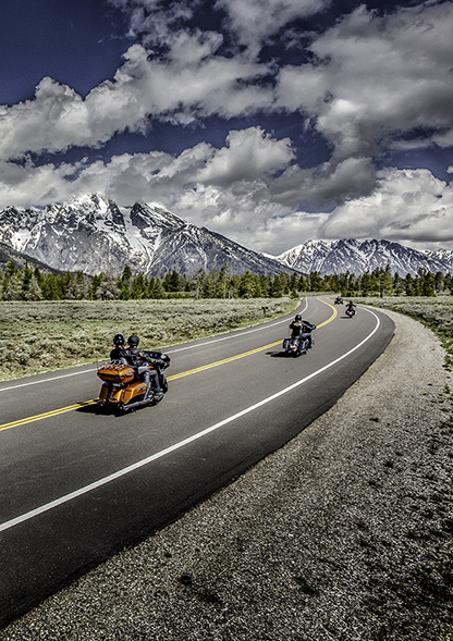 Riders cruise into the horizon on mountain highway